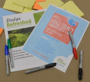 Desk of Post-it notes, markers, and Dodge County brochures.