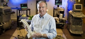 Richard Robb, Ph.D., emeritus, holding spine model in front of Physiology and Biomedical Engineering Equipment