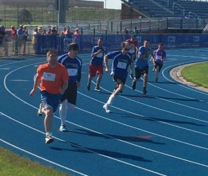 Athletes rounding the track competing in the 400 meter run.  Photo Credit LeAnn Bieber and Lori Torgerson