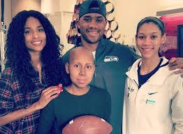 "Russell Wilson and his family visiting children at the Seattle Children's Hospital on ""Blue Tuesday."""