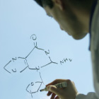 health care provider writing chemical formula on board