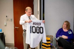 Dr. Charles Rosen is presented with a shirt commemorating his 1,000th liver transplant.