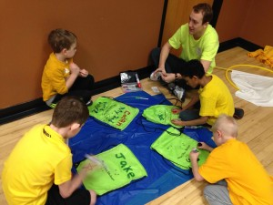"A medical student helps his ""yellow team"" teammates decorate bags to carry their items in throughout the day of Sibshops"