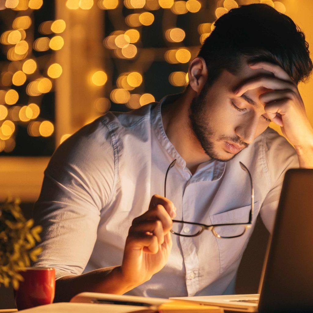 شاب يجلس على جهاز كمبيوتر محمول ويده على جبهته ويبدو متعبًا أو مرهقًا