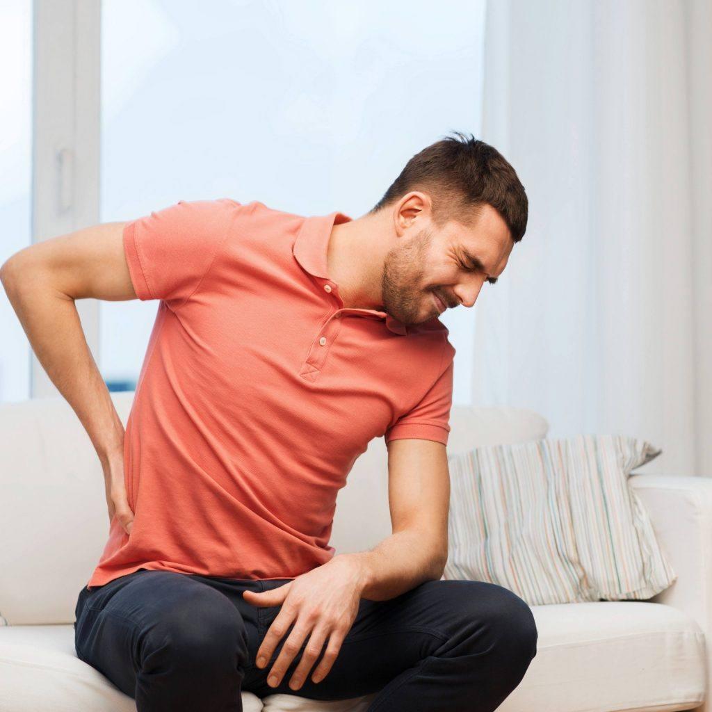 رجل يجلس على أريكة ويده على ظهره يكشف الألم