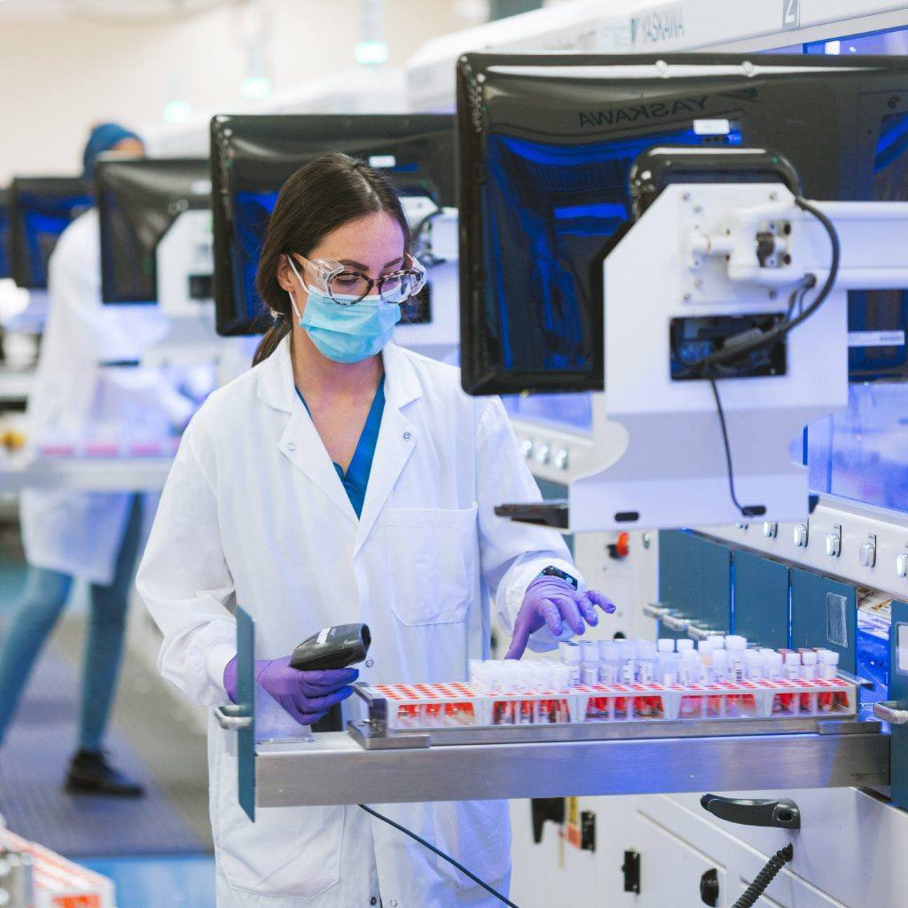 باحثة في الرعاية الصحية في مختبرات مايو كلينيك ترتدي نظارات و معدات الحماية الشخصية والواجهات وقفازات أثناء عملها في المختبر باستخدام أنابيب الاختبار