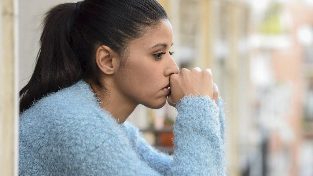امرأة حزينة شابة جميلة في شرفة الشقة تبحث مكتئبًا