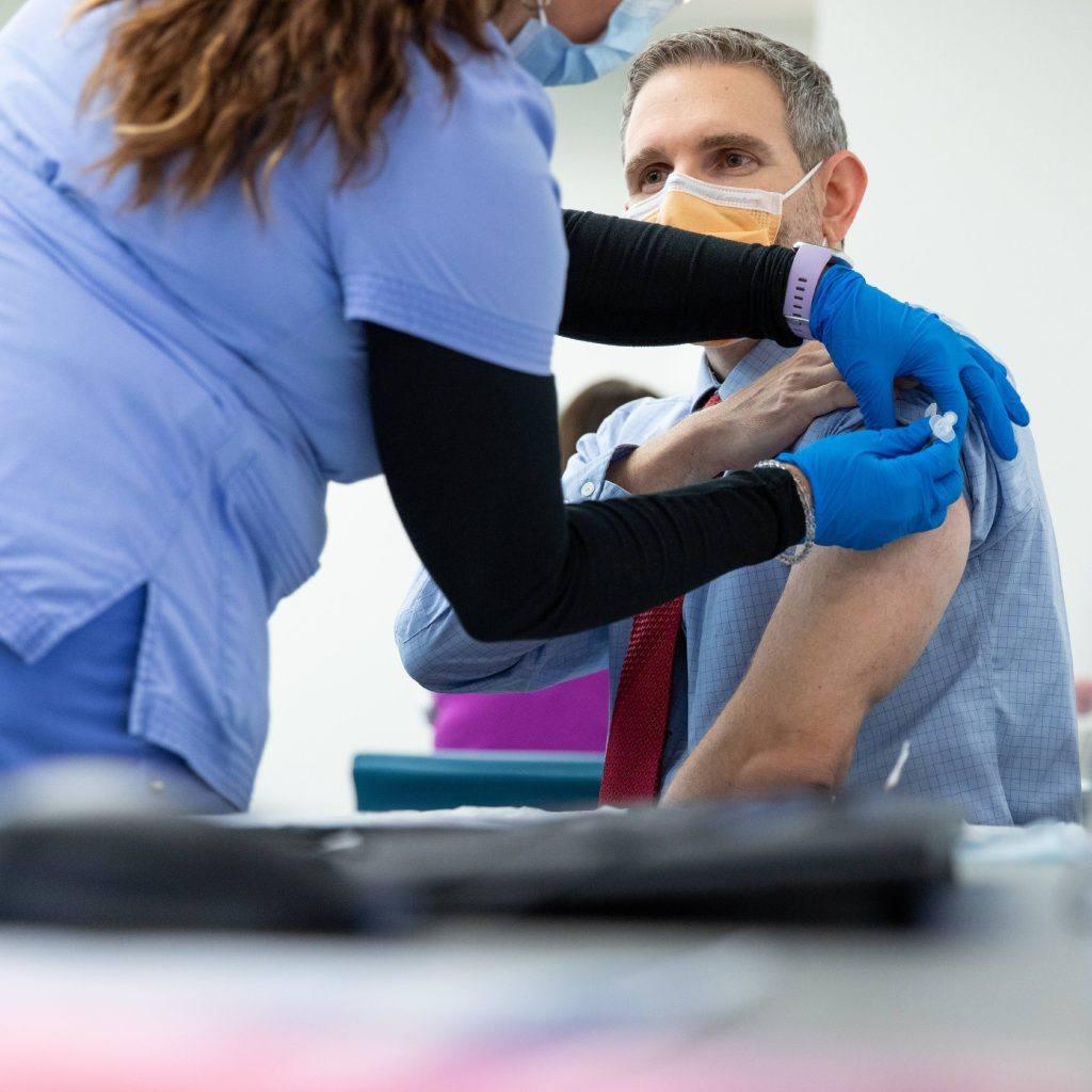 رجل في منتصف العمر يتم تطعيمه ضد COVID-19 من قبل عاملة رعاية صحية