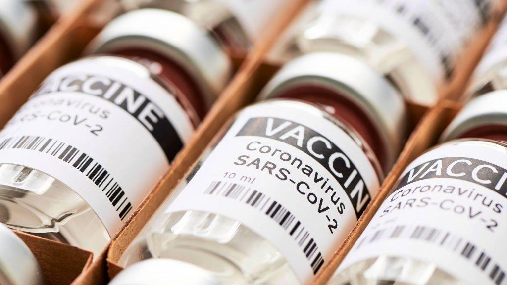 قنينات مختبرية عديدة تحمل اسم لقاح فيروس كورونا COVID-19 SARS-CoV-2 في صندوق توصيل