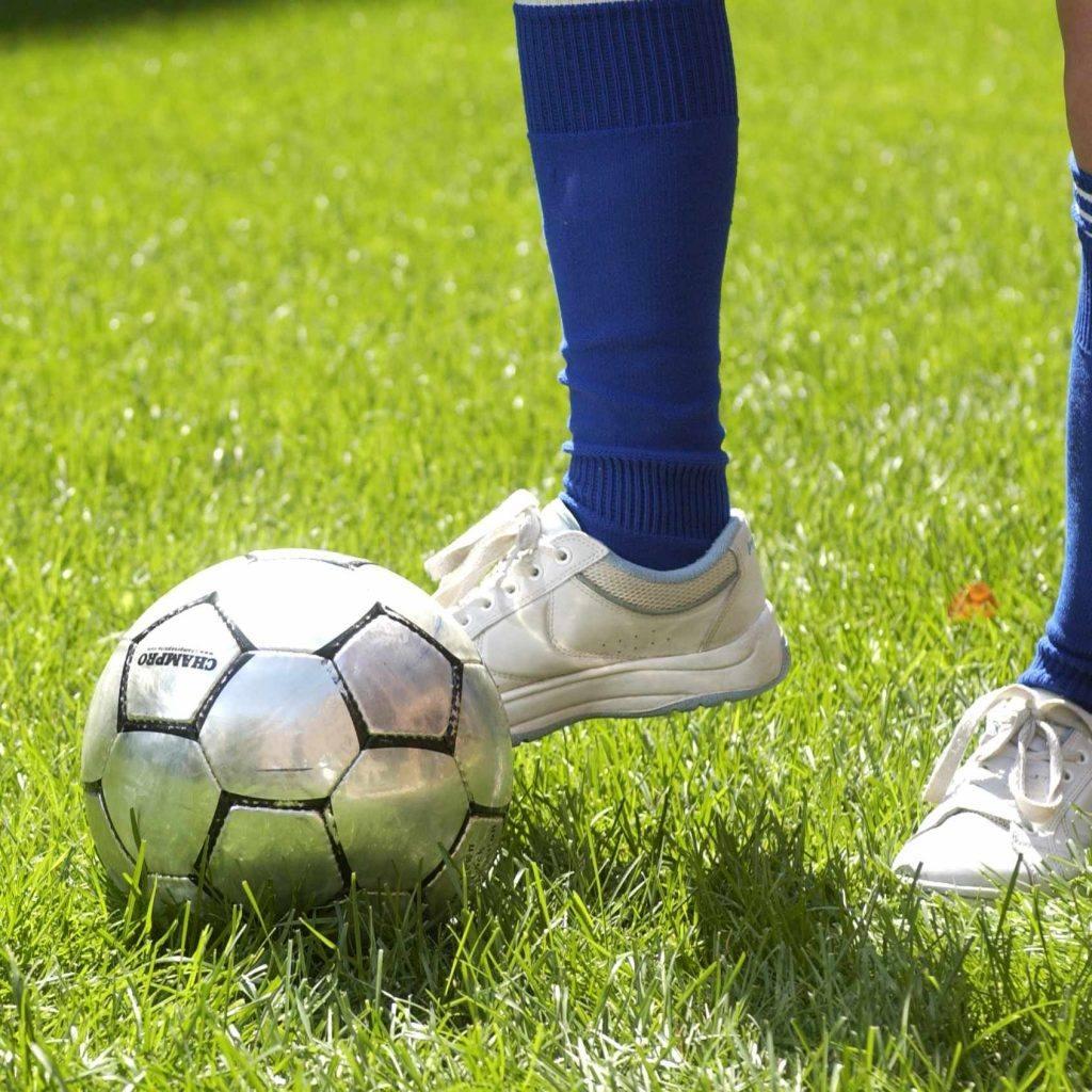 القدم والساق بجانب كرة القدم ؛ ركل القدم كرة القدم
