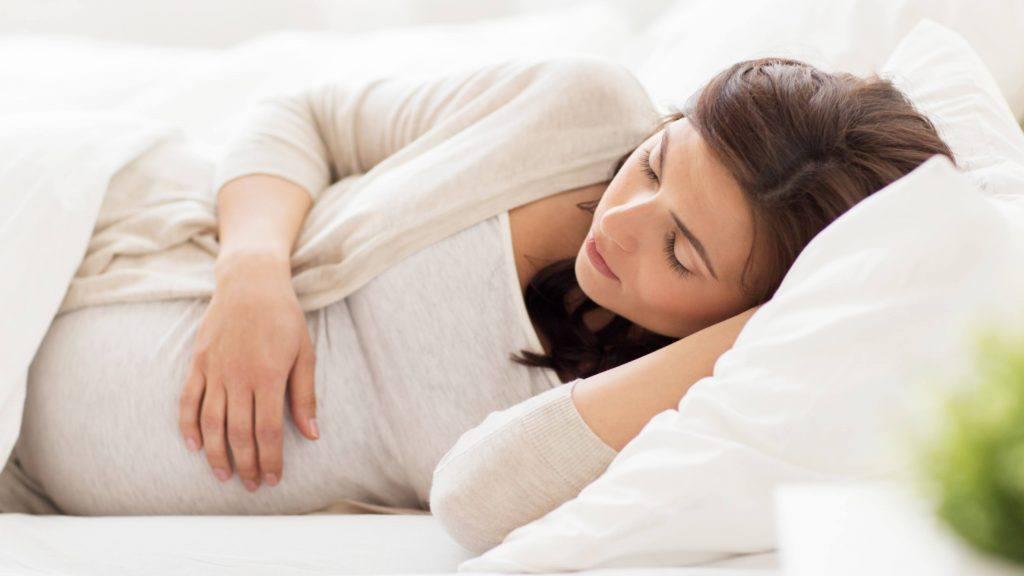 سيدة حامل عيناها مغلقتان وتضع يدها على بطنها بينما تنام في سرير عليه ملاءات ووسادة بيضاء