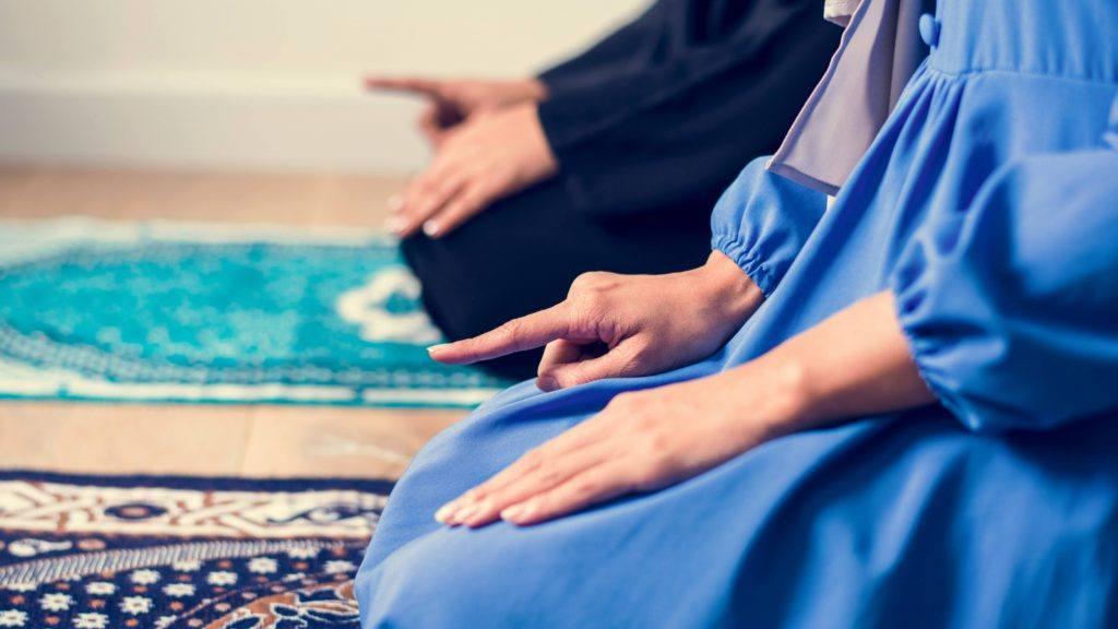 شخصان راكعان على سجادة الصلاة ويصليان