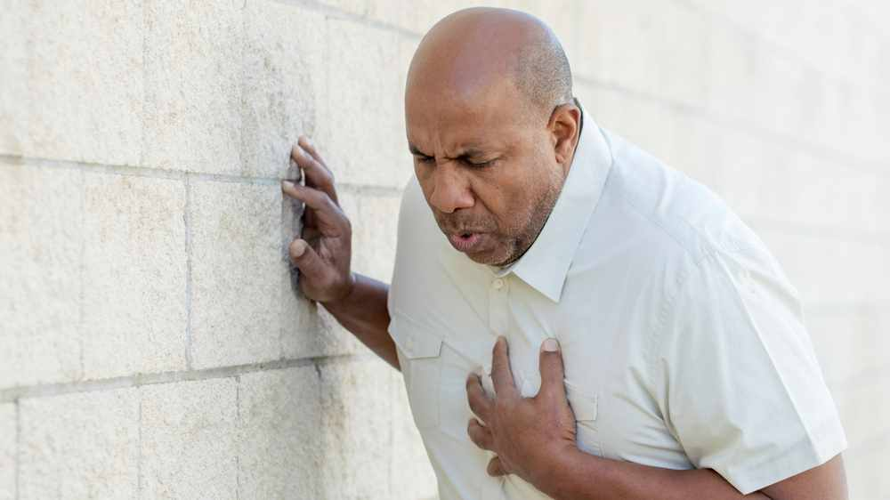 a-middle-aged-African-American-man-holding-his-chest-and-leaning-against-a-wall-maybe-a-heart-attach-or-stroke-16x9