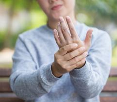 Neuropathy (women rubbing hand)