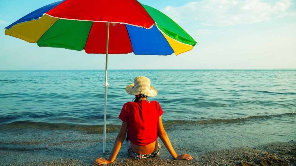 person-sitting-on-the-beach-in-a-hat-under-the-shade-of-an-umbrella-16-x-9