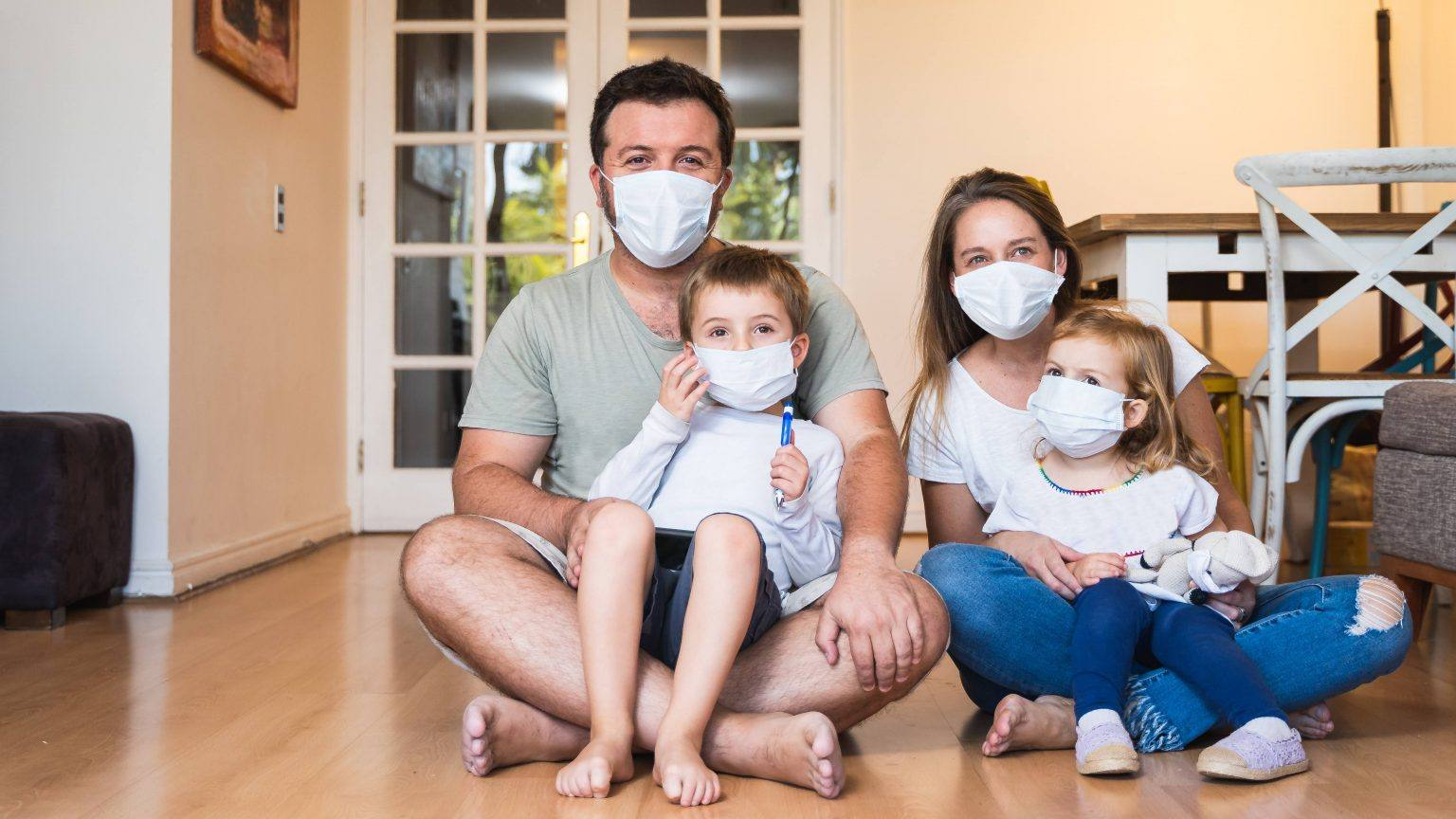 a-white-man-and-woman-with-two-white-children-sitting-on-their-laps-on-the-floor-smiling-and-wearing-face-masks-16x9-1-1536x864