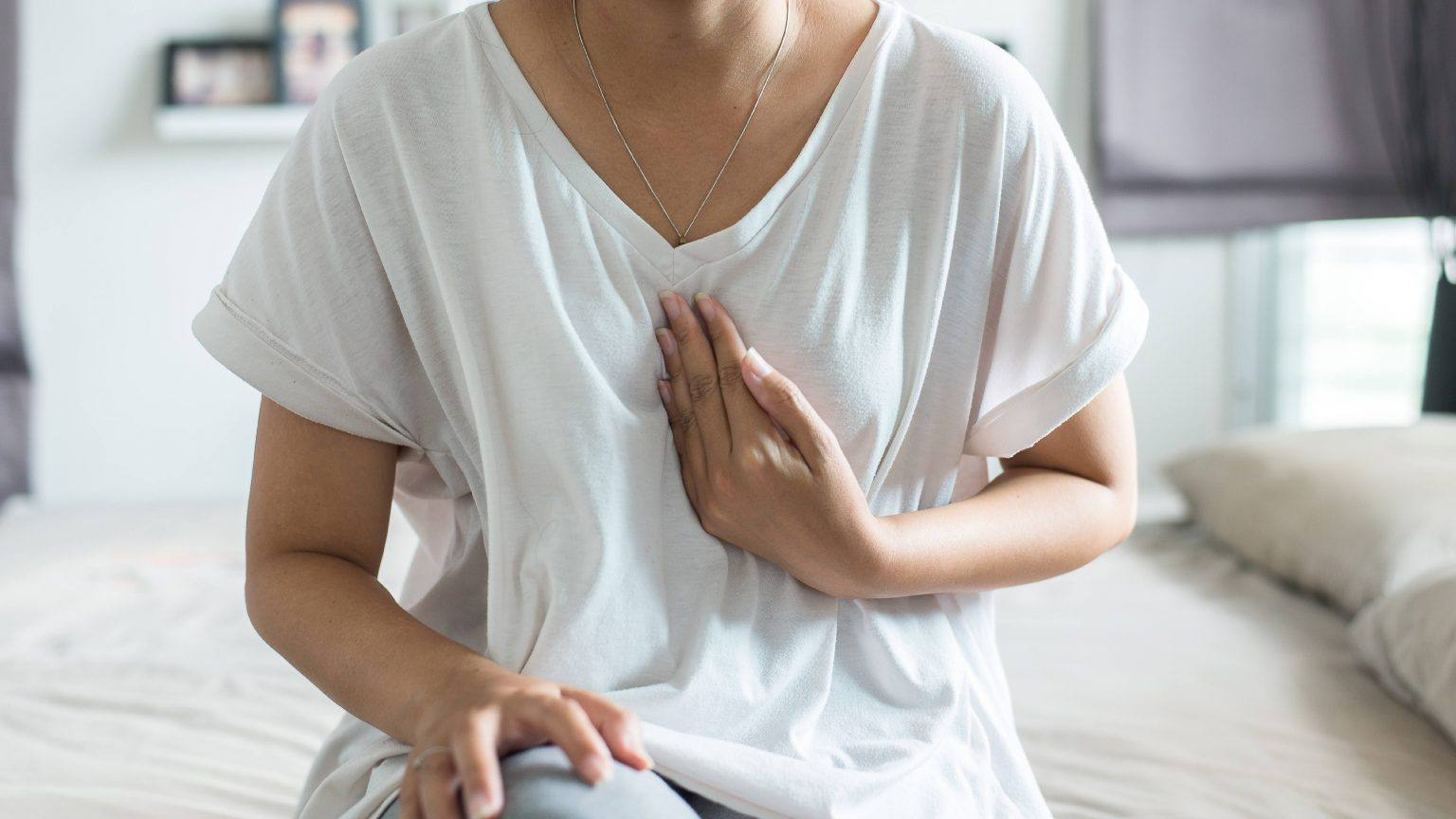 a-white-or-perhaps-a-Latina-woman-in-a-white-t-shirt-sitting-on-the-edge-of-bed-holding-her-hand-to-her-chest-out-of-concern-stress-worry-heart-pain-16x9-1-1536x864