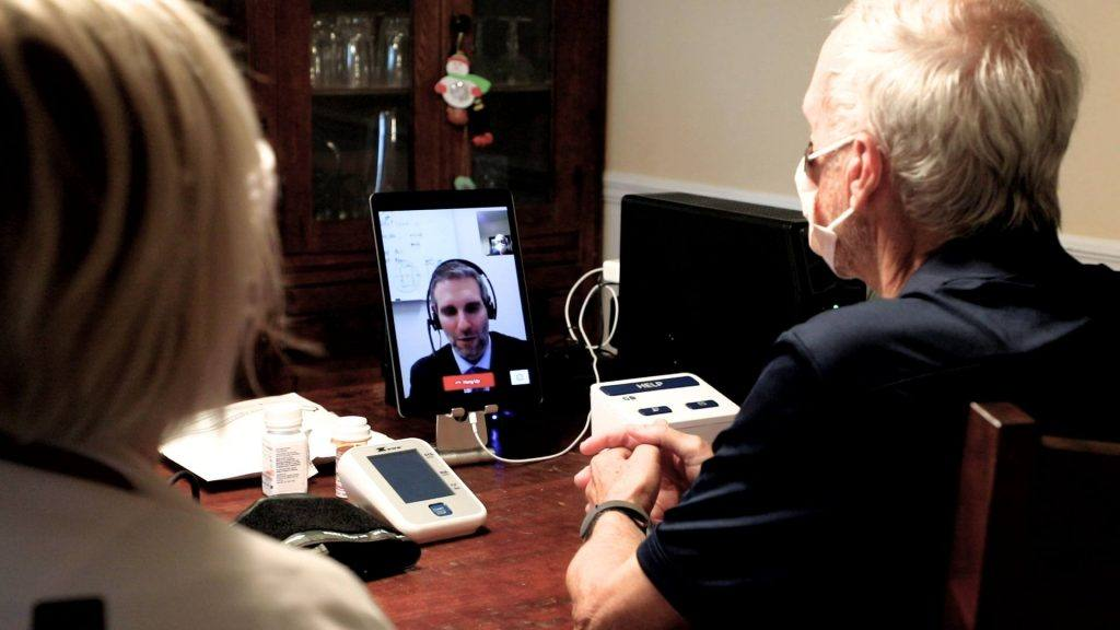 Advanced-Care-at-Home-patient-John-Jolly-sitting-at-his-dining-room-table-talking-with-a-Mayo-doctor-on-a-telehealth-monitor-16x9-1-1024x576