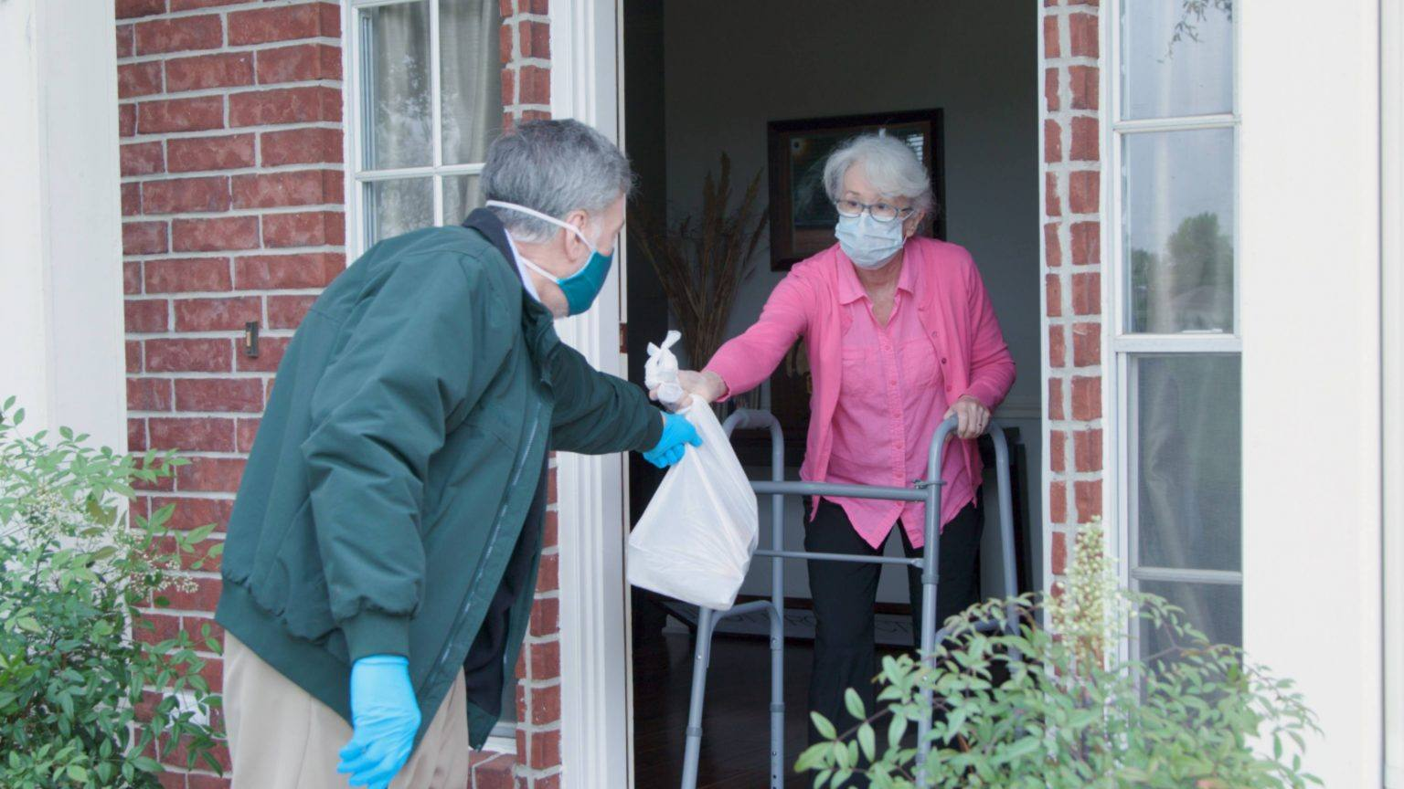 a-white-middle-aged-man-wearing-a-mask-and-gloves-delievering-food-to-an-older-white-woman-also-wearing-a-mask-at-her-front-door-during-COVID-19-pandemic-16x9-1-1536x864