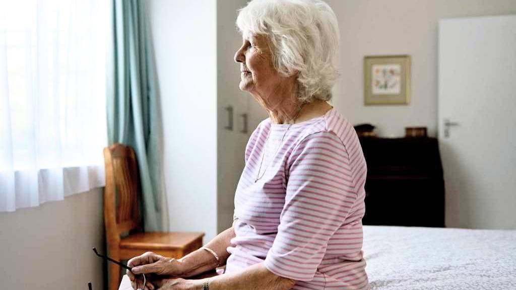 older-woman-sitting-alone-on-a-bed-and-thinking-16x9-1