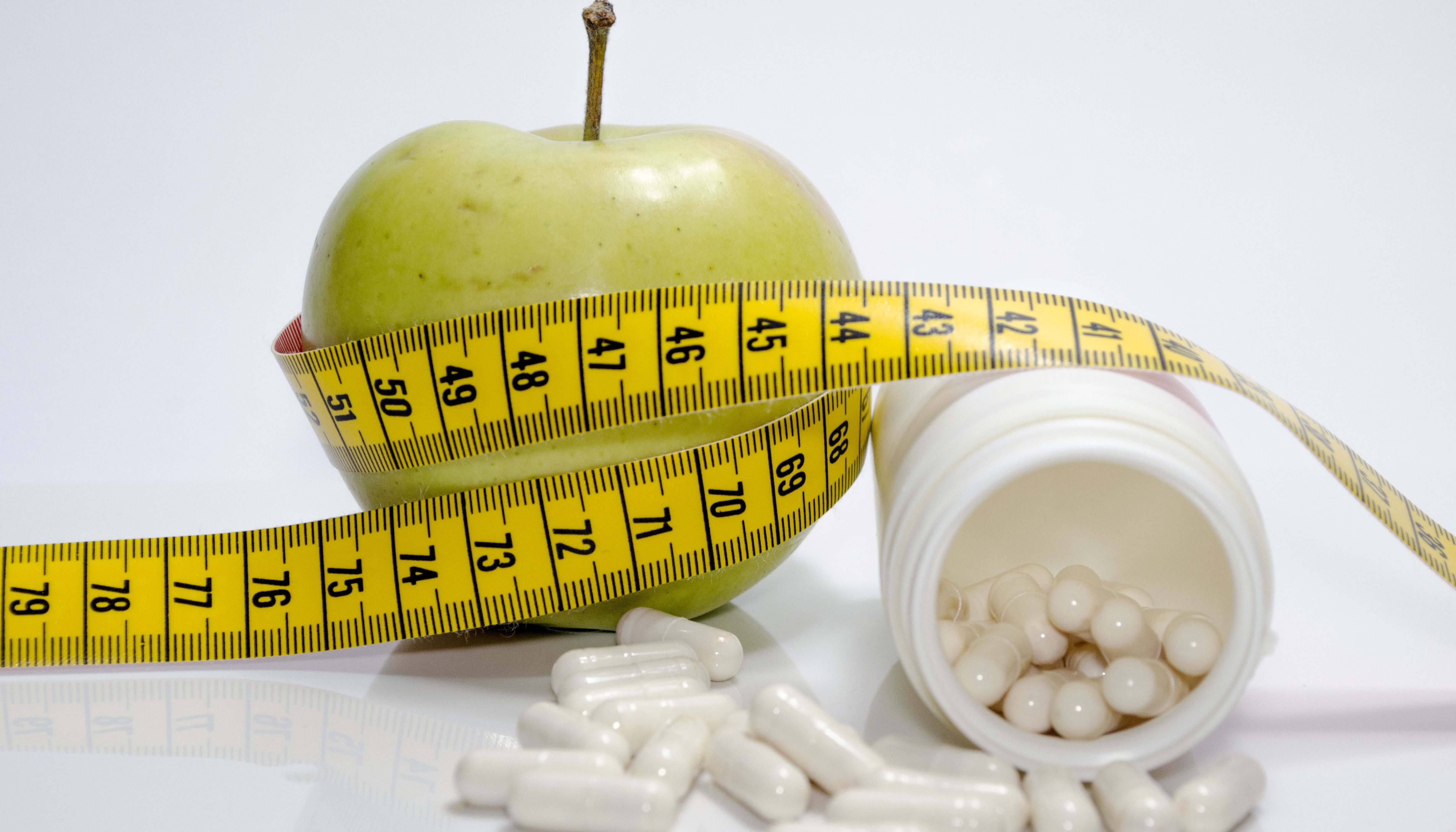 Generic medication, apple, and measuring tape