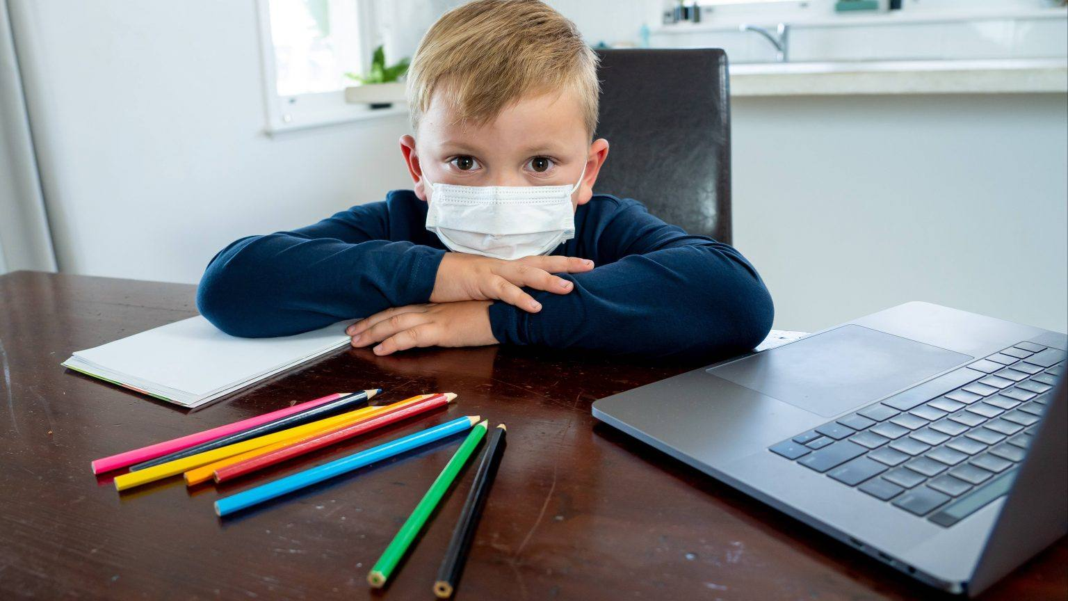 a-little-white-boy-looking-sad-and-lonely-wearing-a-mask-and-sitting-at-a-desk-with-school-paper-colored-pencils-and-a-laptop-computer-16x9-1-1536x864