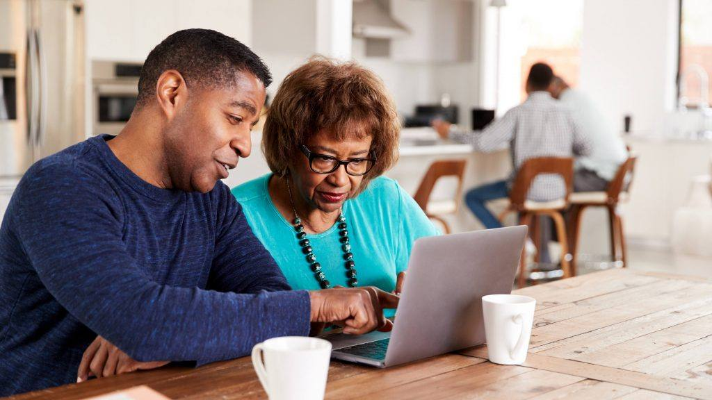 a-middled-aged-man-helping-an-older-woman-with-something-on-the-screen-of-a-laptop-16X9-1024x576