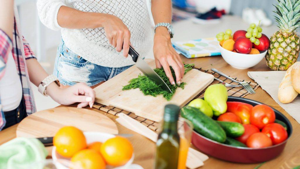 a-woman-slicing-and-cutting-up-fresh-fruits-and-vegetables-on-a-kitchen-counter-16x9-1024x576