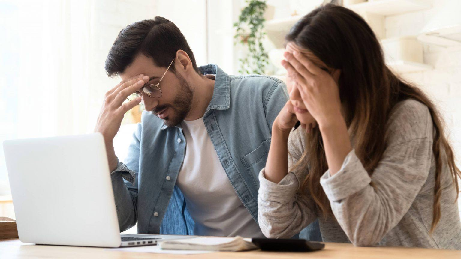 a-young-couple-a-white-man-and-a-white-woman-sitting-together-at-a-kitchen-table-looking-stressed-sad-worried-while-working-on-a-computer-16x9-1-1536x864