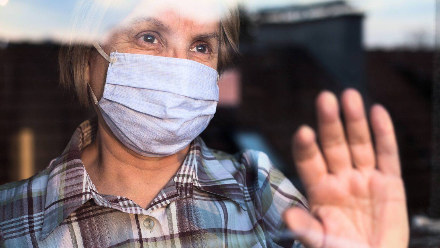 an-elderly-white-woman-wearing-a-face-mask-and-holding-her-hand-up-on-a-window-looking-outside-and-seeming-sad-isolated-16x9-1-1536x864