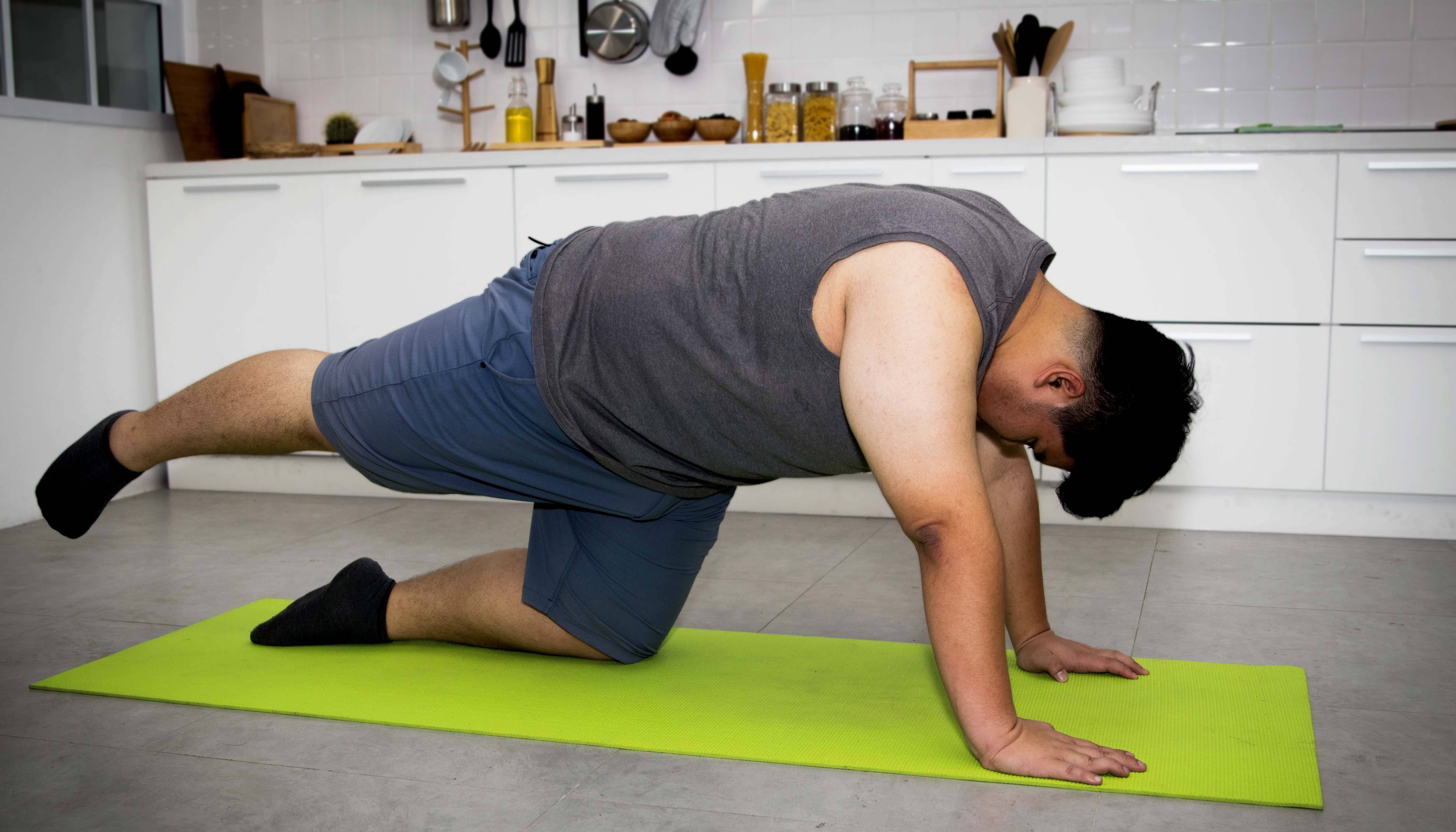 Man exercising in kitchen on a yoga mat