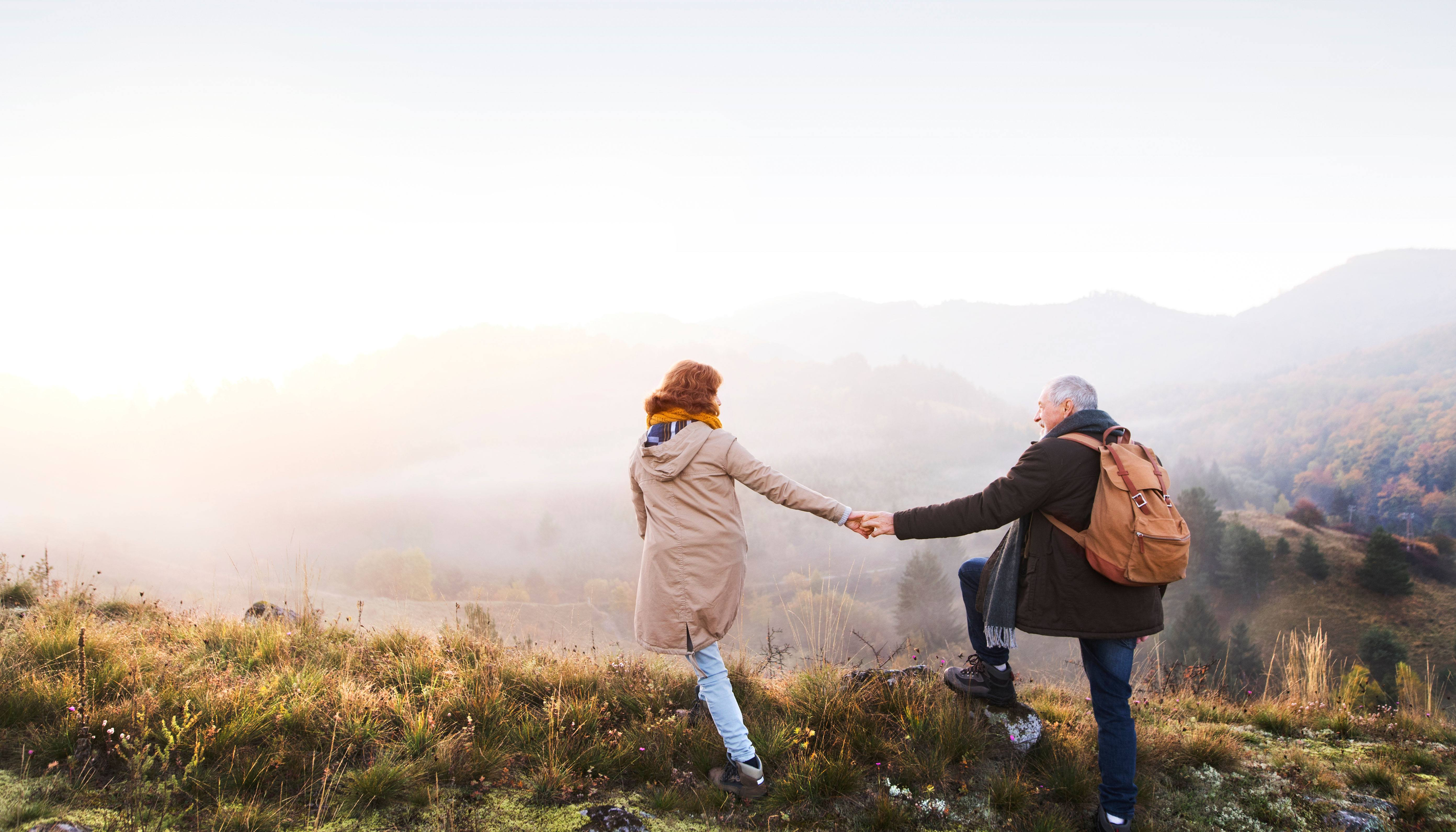 Older Couple holding hands on a foggy hill