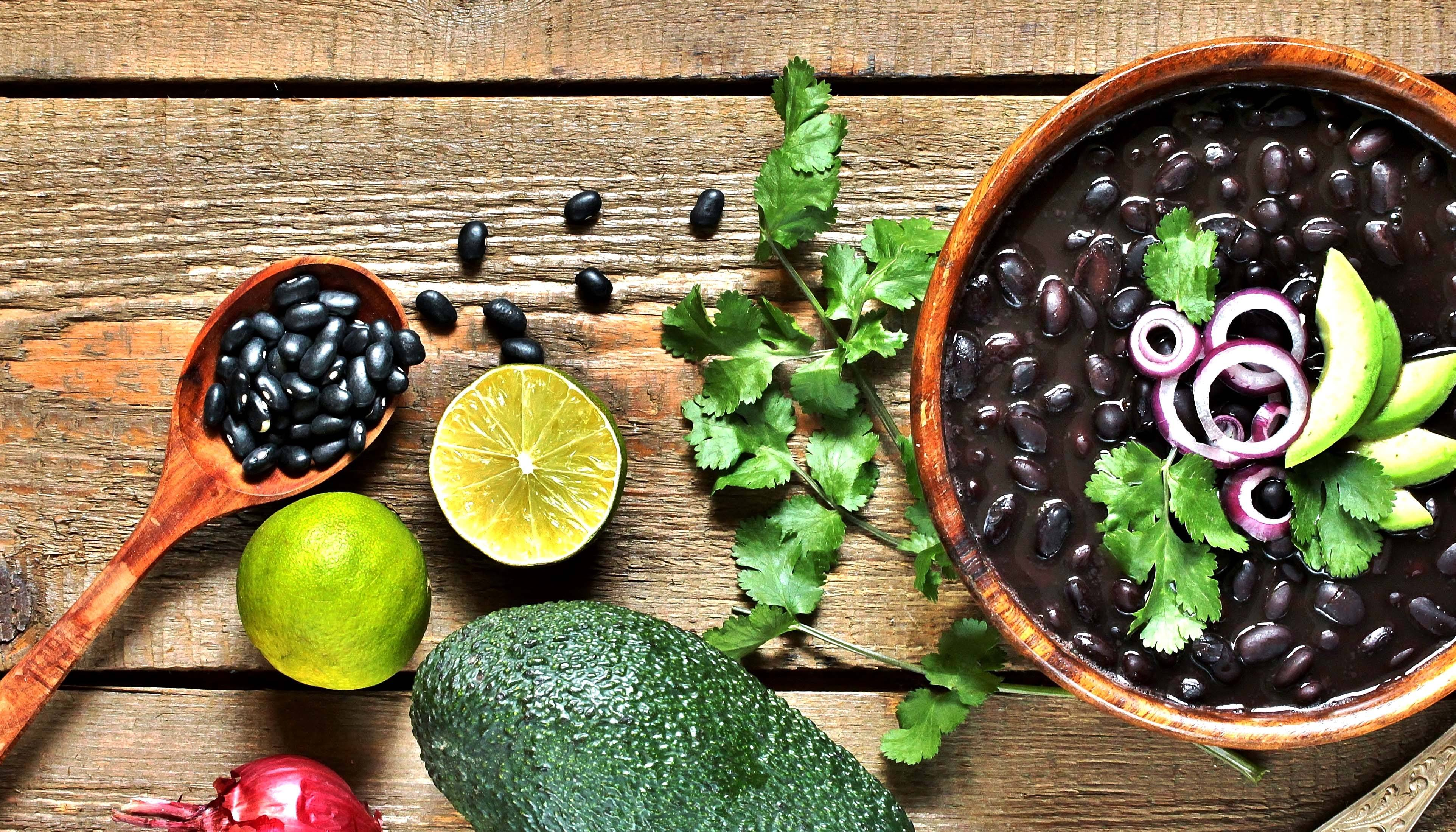 Lime, avocado, and bowl of black beans