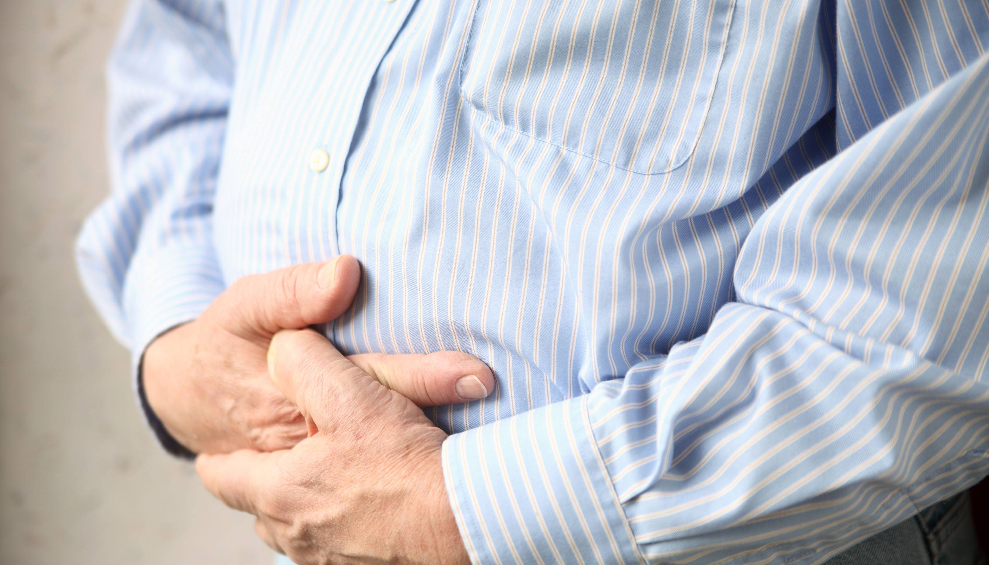 Male holding hands over stomach