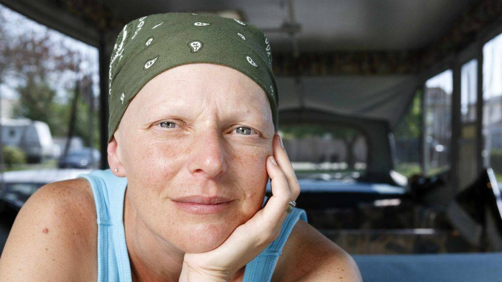 a-woman-with-a-headscarf-perhaps-due-to-chemo-therapy-treatment-for-cancer-looking-pensively-into-the-camera-16x9-1024x576