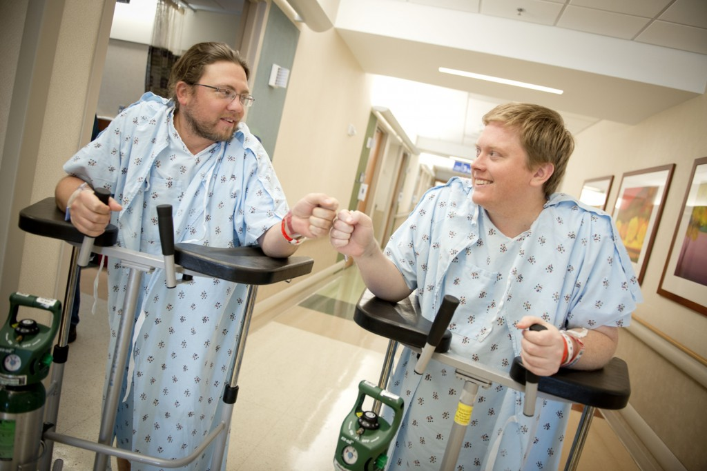 Adam Gray (left), kidney donor, shares a fist bump with his cousin and kidney transplant recipient Trey Sullivan.