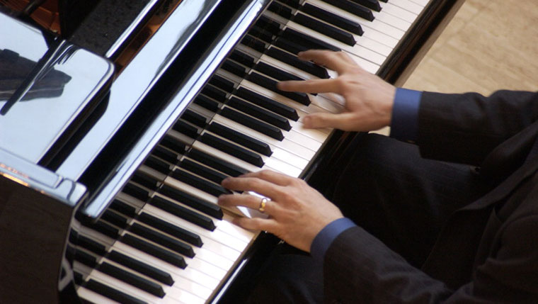 Photo of hands playing piano.
