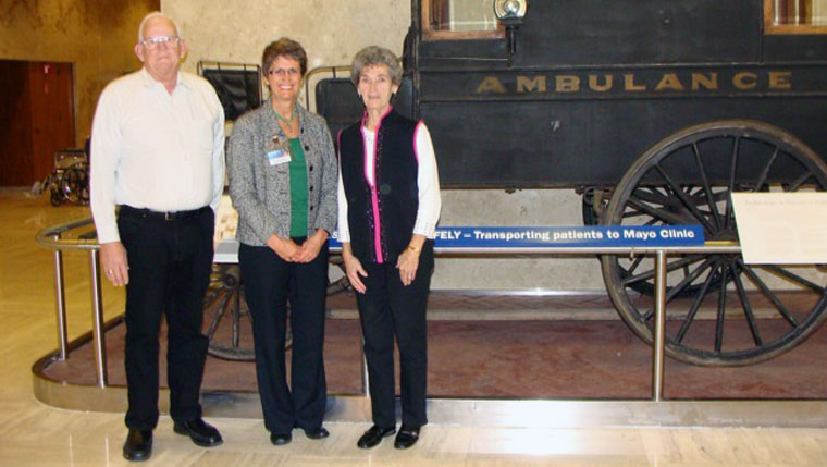 Dave and Joan Hittner pose with a historic ambulance in the Matthews Grand Lobby of the Mayo Building in Rochester.