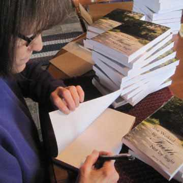 "Jenny Peterson signs copies of her book, ""She Walked by Faith, Not by Sight."""