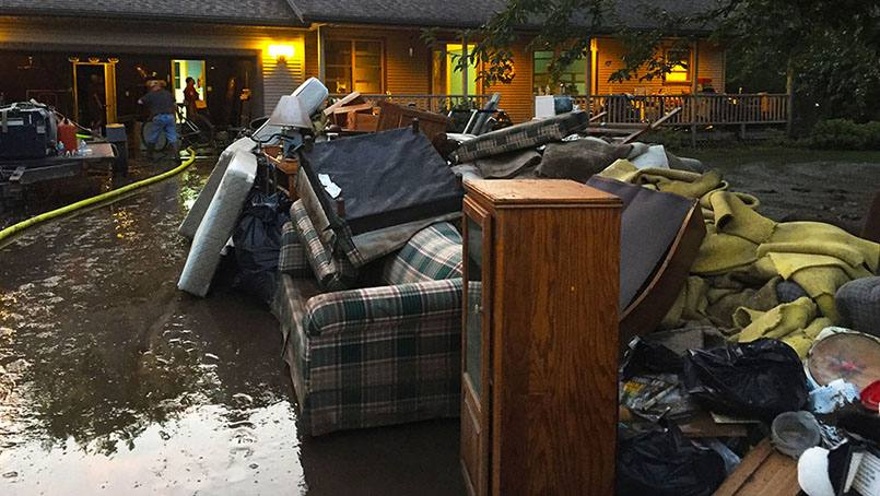 Colleagues and other volunteers helped clear waterlogged furniture and other items from the home of Lynn Luloff.