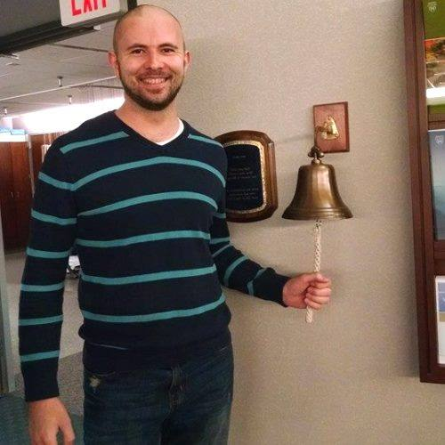 Travis McGinnis rings bell after cancer treatment.
