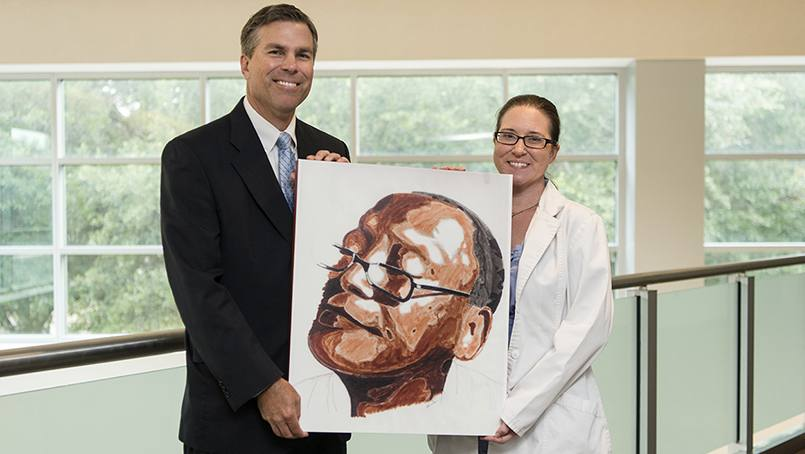 Ryan Uitti, M.D., and Beth McAllister with a self-portrait of patient Tyrone Nanton.