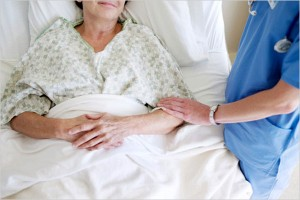 Hospital bed with patient and care giver touching her arm
