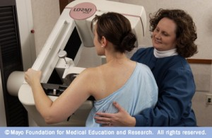 picture of medical tech helping patient position for a mammogram