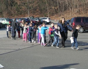 photo of children walking in parking lot with adult