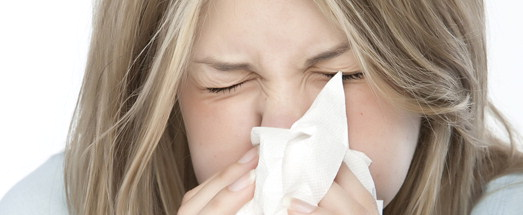Young girl sneezing into tissue