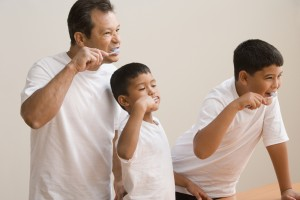 Father and sons brushing teeth