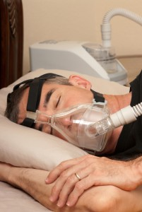 Man sleep with CPAP mask for sleep apnea.