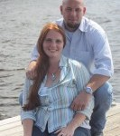 Jessica and her husband standing outside on pier with water in the background
