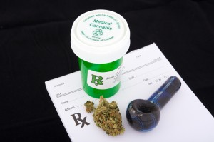 A vial labeled medical cannibis, some marijuana and a small pipe on a prescription pad.